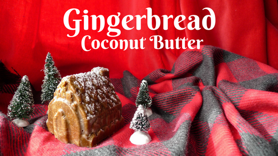 Brown gingerbread coconut butter molded into a house with powdered sugar dusted on top. The house sits on a red and grey plaid fabric and is surrounded by miniature Christmas trees.